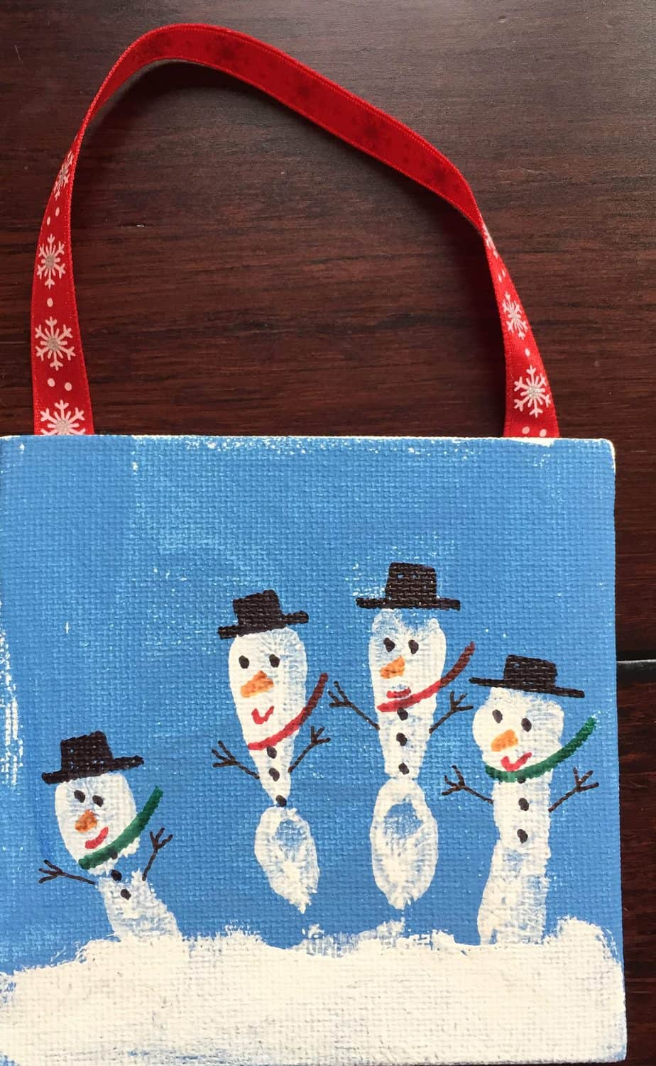 Small canvas with finger prints made into snowmen is an easy Winter crafts for kids