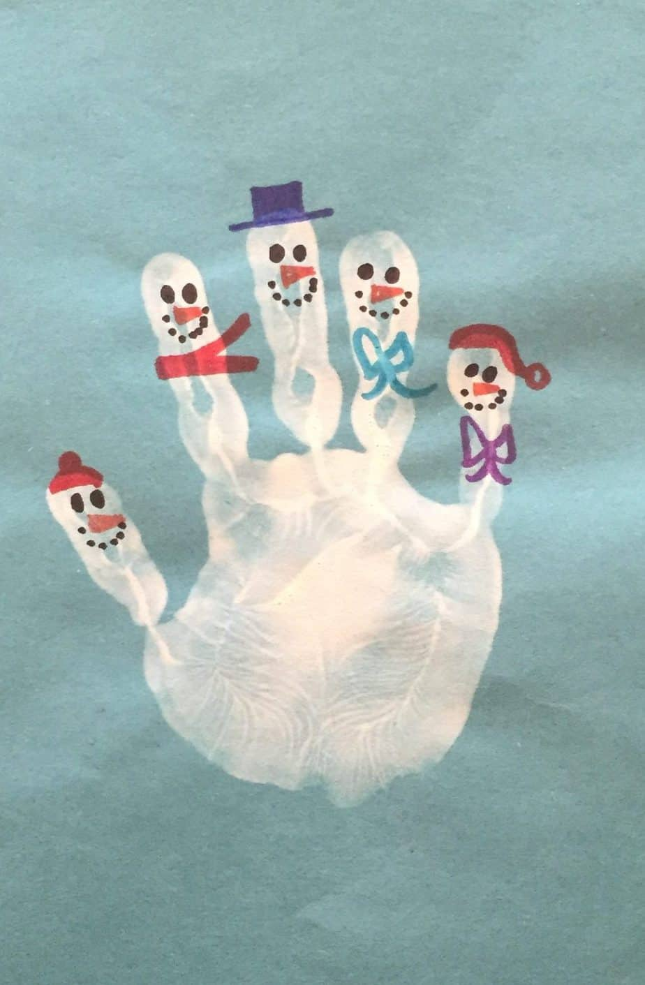 White hand-print with fingers made into tiny snowman is a simple winter craft for kids.