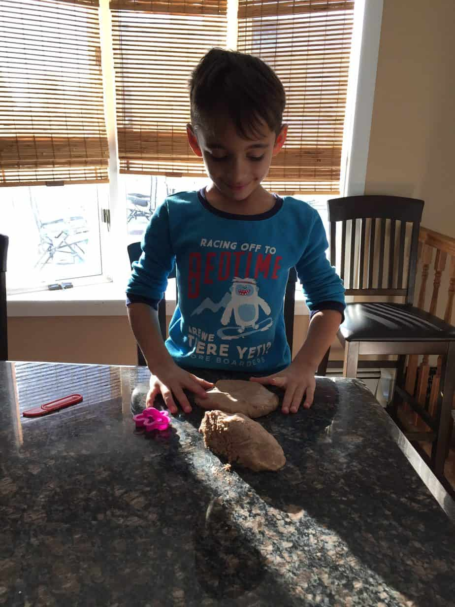 Young boy in blue pajamas playing with gingerbread play dough