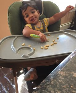 A toddler boy sitting in a high chair eating pasta . Having your toddler practice feeding is something that's included in a toddler daily home schedule.