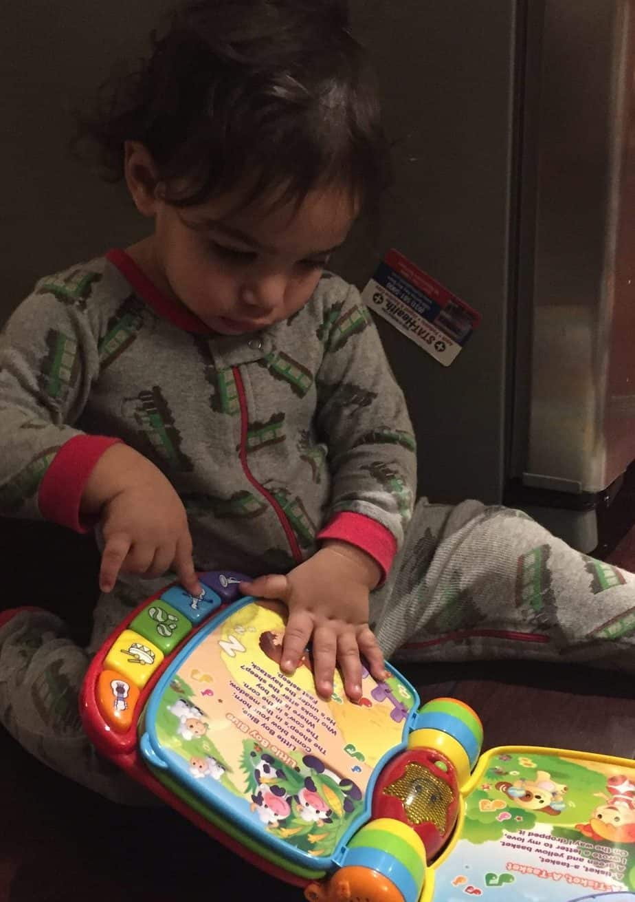 Little boy reading a musical boy is a great toddler toy under $20.