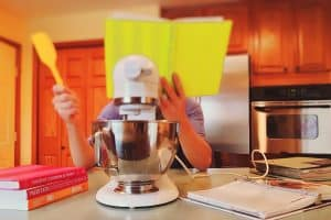 Child holding a cooking book in front of a large mixer in a the kitchen. Showing how to get kids cooking and involved in the kitchen