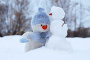Small snowmen next to a stuffed snowman to make a fun outdoor winter activity.