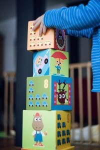 A child stacking blocks is a simple way to build fine motor skills in children