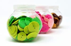 Three containers of colored buttons that are sorted. Sorting buttons is a simple fine motor activity for toddlers to do at home