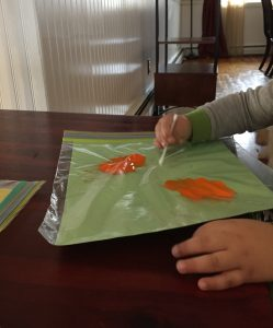 Child painting with paper inside a plastic bag is a clean way to paint and build fine motor skills.