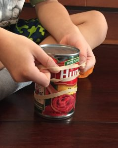A child putting rubber bands over a can is an at home way to build fine motor skills