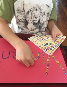 Child using stickers to cover his name is an easy way to build fine motor skills.