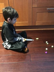 A boy using a turkey baster to move pom poms is a cheap way to build fine motor skills