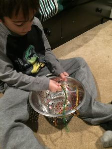 A boy sitting on the floor putting pipe cleaners into a strainer is a way to build fine motor skills in toddlers
