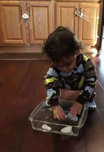 Toddler playing with ice cubes is a great activity to add to your daily home schedule