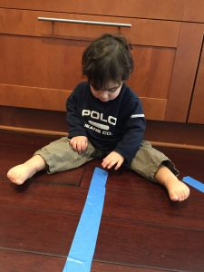 A child trying to pull painters tape off the floor is an exciting way to build fine motor skills in toddlers