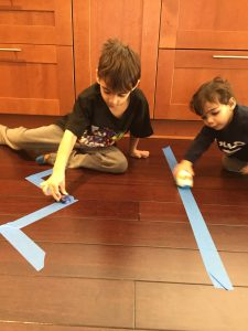 Two boys having a car race on painters tape is a fun way to build fine motor skills
