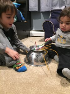 A child and a toddler putting pipe cleaners into a upside down strainer is a way to build fine motor skills in toddlers.