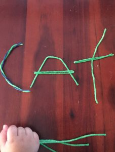Using wikki sticks to spell CAT is an at home way to build fine motor skills