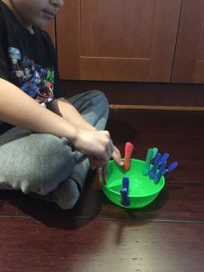 A child sitting on the floor using clothes pins on a bowl is a simple way to build fine motor skills.