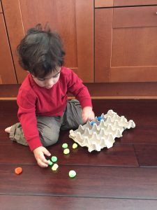 A child in a red shirt picking up pom poms to put into an egg carton is a simple way to build fine motor skills in toddlers