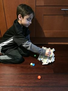 A boy putting poms poms into a egg carton is a cheap way to build fine motor skills