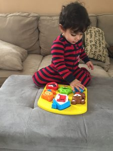 A toddler playing with a chunky puzzle is a great way to build fine motor skills in toddlers