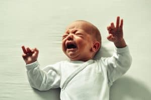 Dealing with a Milk Allergy in Babies. Baby in a white shirt crying and arms in air.