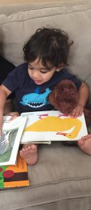 Little boy reading with his teddy bear. A good example of toys for Toddlers under $20 are books.