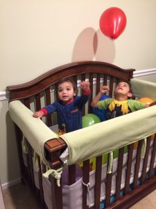 Two boys in the crib playing with balloons. Balloons are an easy gross motor activities.