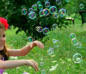 Young girl playing with bubbles outside is a nice activity to develop gross motor skills