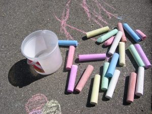 Chalk laid out on a blacktop. Playing with chalk is a gross motor activity.