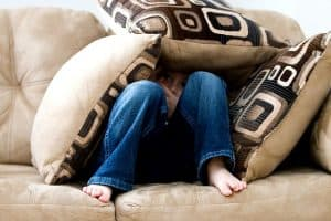 Child hiding under three pillows. Activities to Develop Gross Motor Skills in Children.