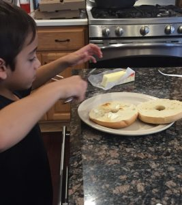 Young child putting butter on a bagel is an easy way to get kids cooking in the kitchen