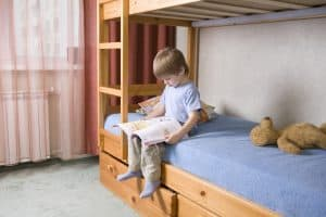 Boy sitting on bed reading. Transitions to help your child go to a big kid room