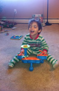 Toddler boy playing a kid drum set.  Musical toys are perfect toddler toys under $20.