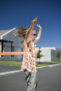 Develop gross motor skills using a hula hoop.