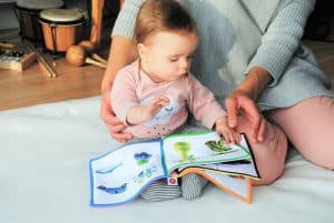 Toddler reading with an adult is part of a toddler daily home schedule.