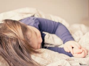 Toddler girl sleeping and a regular sleep routine is part of a healthy toddler home schedule.