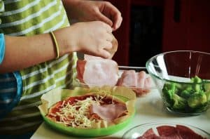 Child making his own pizza is a great way to get kids cooking in the kitchen