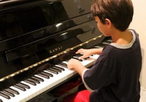 Boy playing the piano. Music lessons are something to think of for a non toy gift for kids