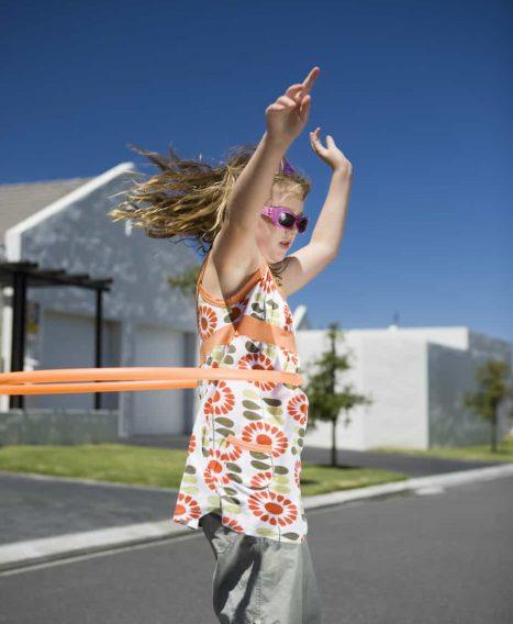 Develop gross motor skills using a hula hoop.