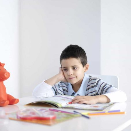 Boy sitting at table being bored. What to do when your child says their bored?
