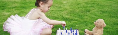 Girl playing chess showing the importance of play in early childhood