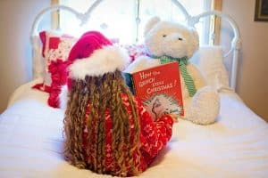 Girl with Santa hat reading a Christmas book sitting on her bed. Reading together is a simple step to get through the holiday craziness and enjoy it.