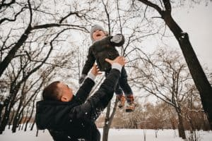 Winter outdoor playtime with a man throwing a toddler in the air outside during winter.